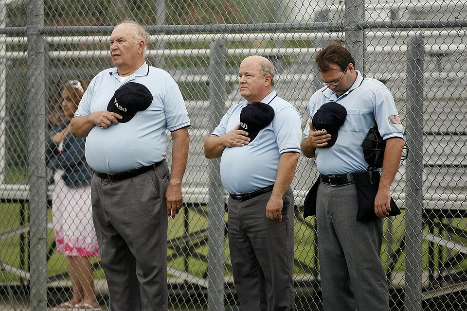 Men holding their hats unto their chest