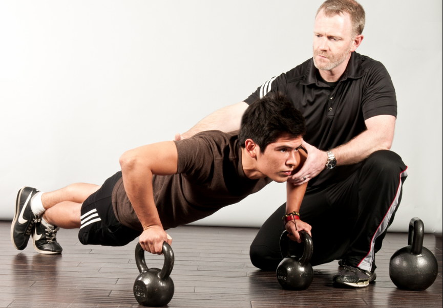 Man doing push ups assisted by his trainer