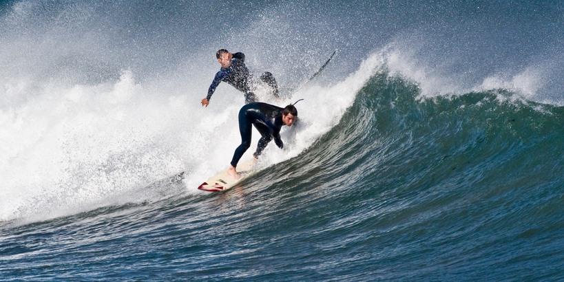 Men surfing catching waves